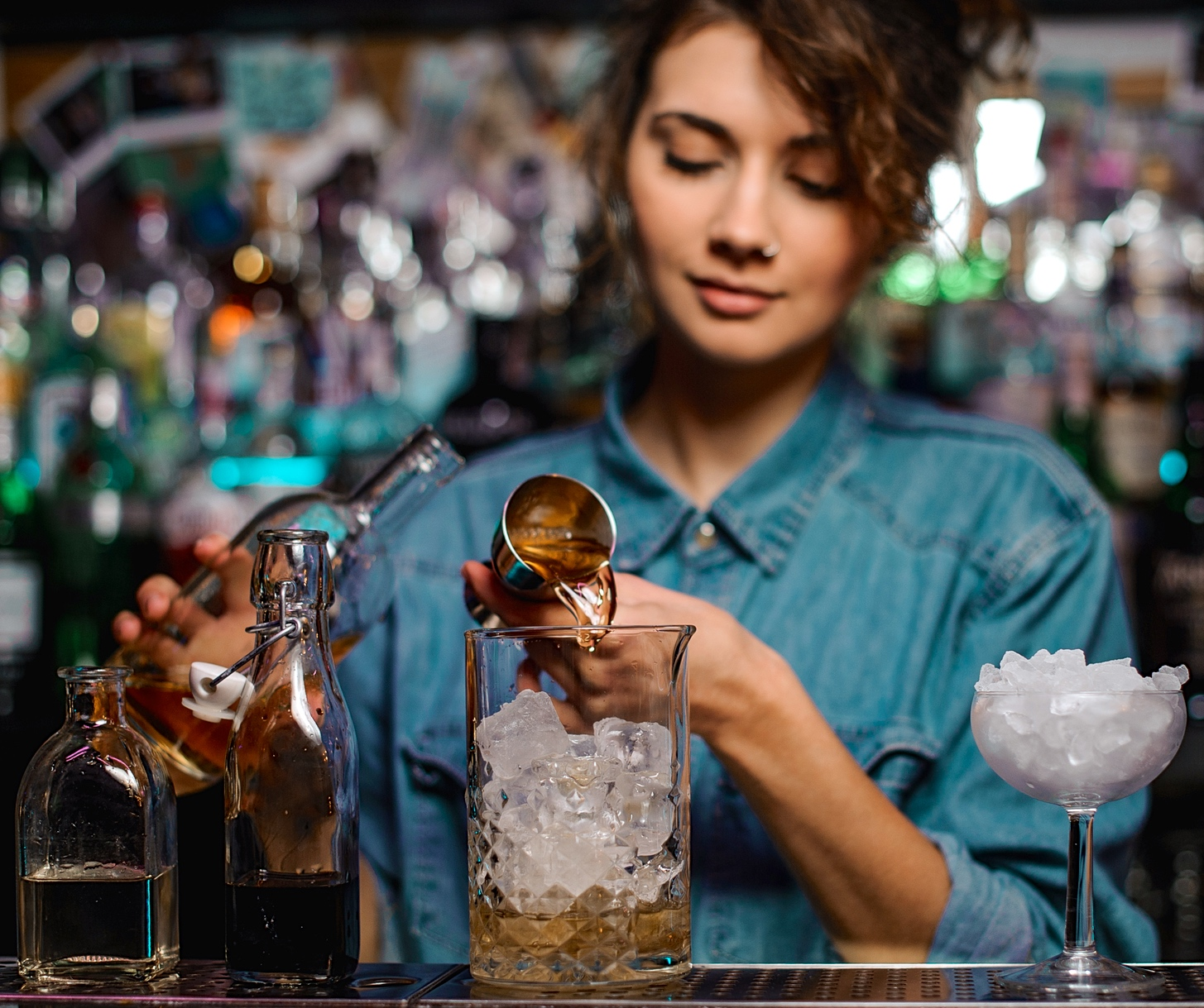 Female bartender Pouring Quickly And Accurately In Your Bar. Use A Jigger, Shot Glass Or Measuring Cup for cocktail